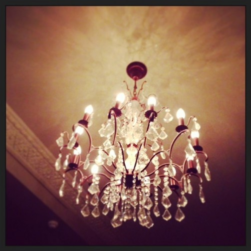 Elegant interior; chandeliers hang from the corniced ceiling